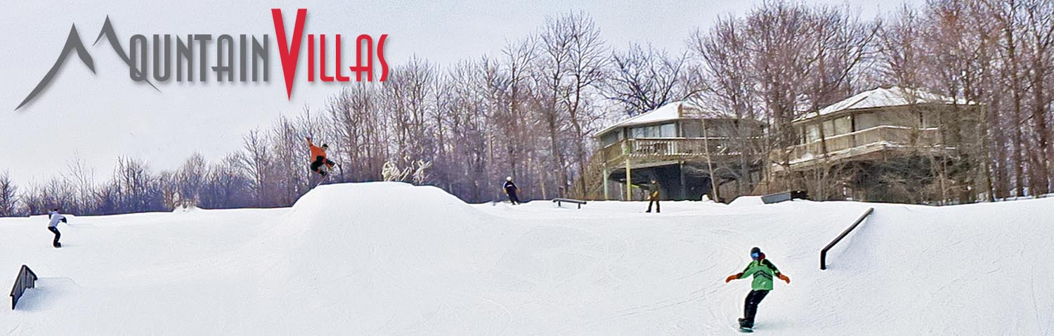 A view of two villas next to the Spirit Mountain Terrain Park where many people are snowboarding